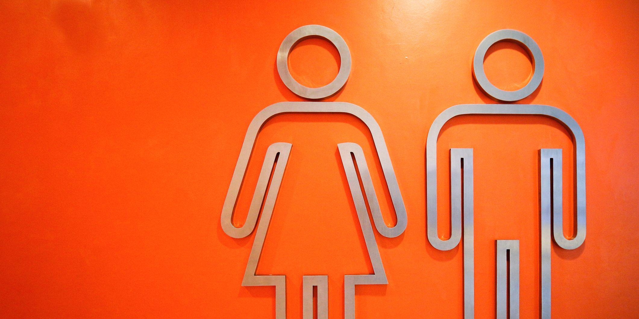 Close-Up Of Metallic Restroom Sign On Orange Wall