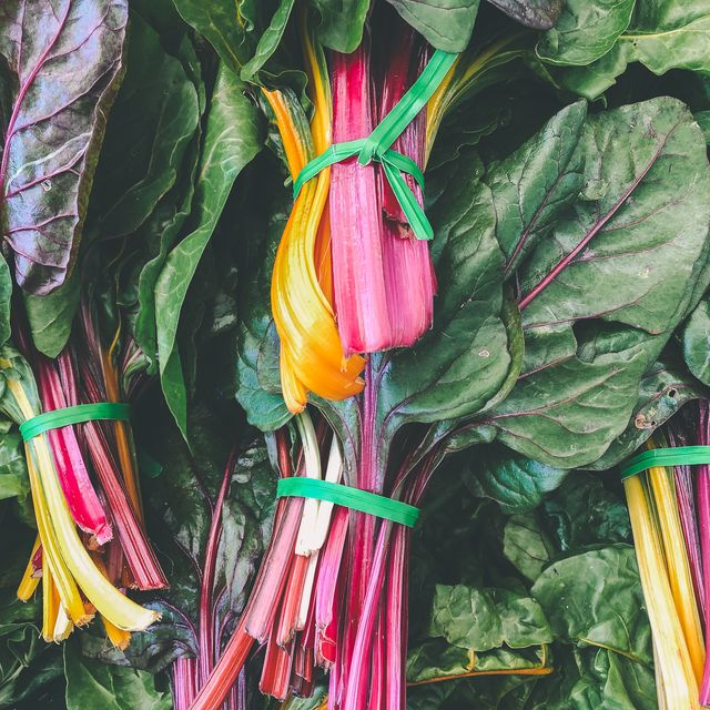close up of multi colored leafy greens for sale in market