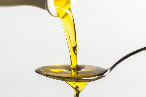 Close-Up Of Olive Oil Pouring On Spoon From Container Against White Background