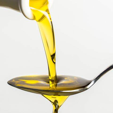 close up of olive oil pouring on spoon from container against white background
