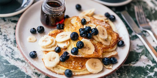 close up of pancakes with fresh bananas and blueberries served for brunch