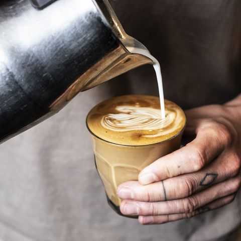 Close up of person with tattooed finger pouring milk from metal jug into glass of cafe latte.