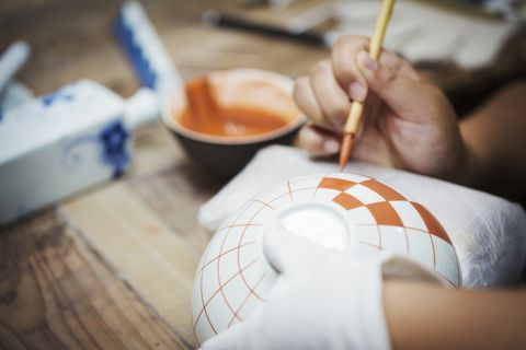 Close up of person working in a Japanese porcelain workshop, painting geometric pattern onto white bowls with paintbrush.