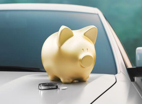 Close-Up Of Piggy Bank And Car Keys On Vehicle Hood