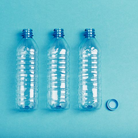 close up of plastic bottle on table against blue background