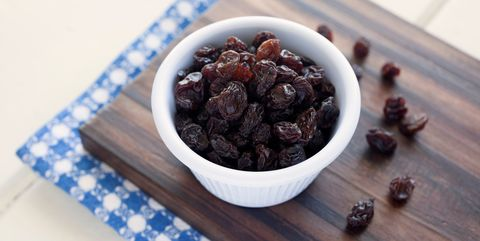 close up of raisins in bowl on cutting board