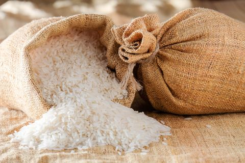 close up of rice spilling from sack on table