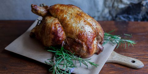 Close-Up Of Roasted Chicken On Cutting Board At Table
