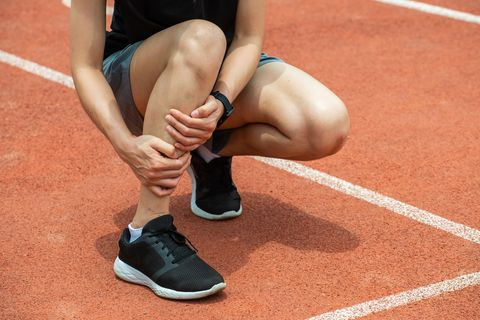 close up of runner woman holding her calf, suffering from calf pain, after running