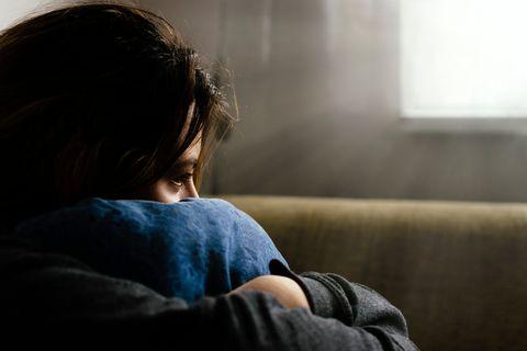 憂鬱症Close-Up Of Sad Woman Hugging Cushion While Sitting At Home