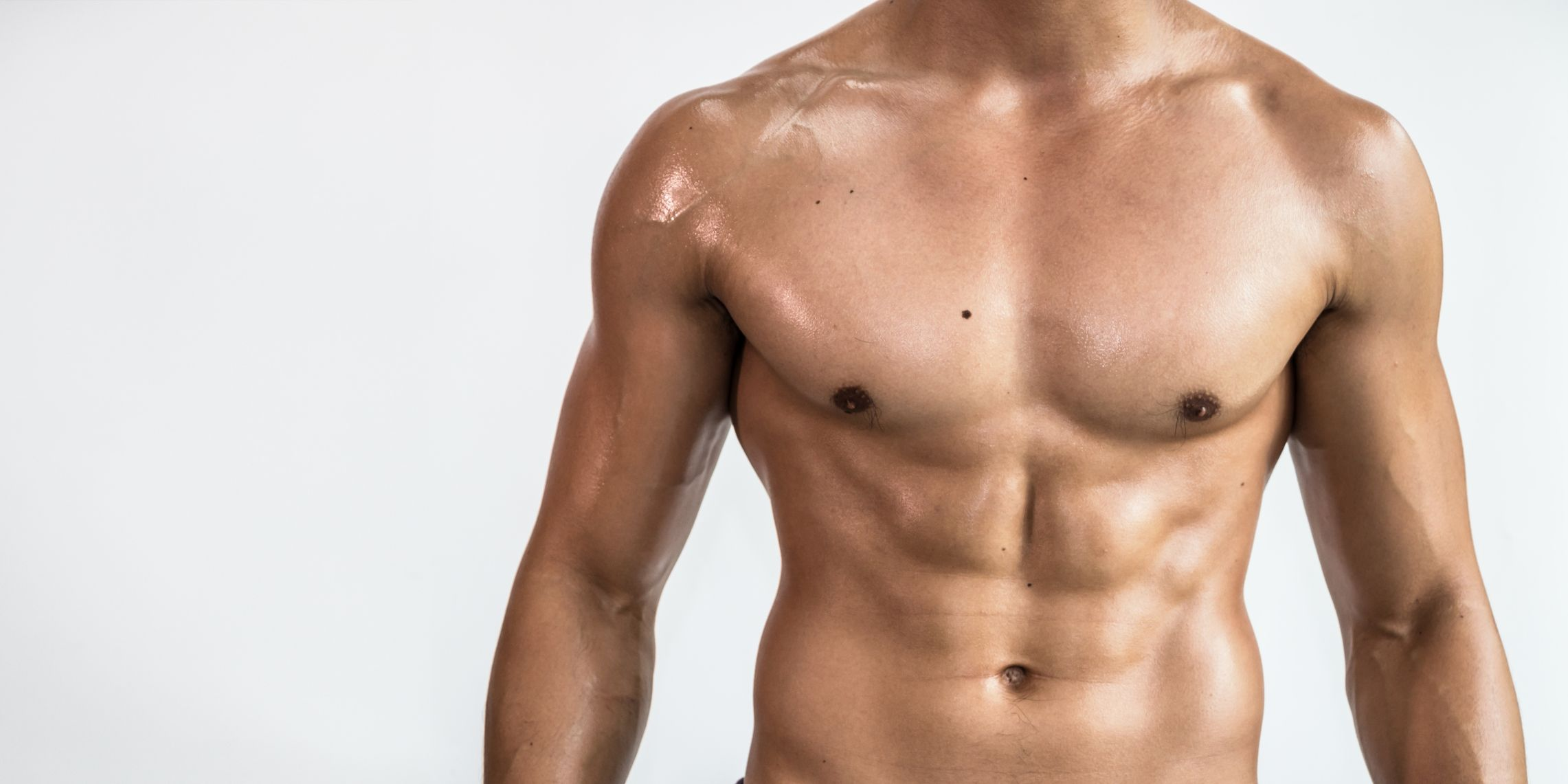 Close-Up Of Shirtless Man Standing Against White Background