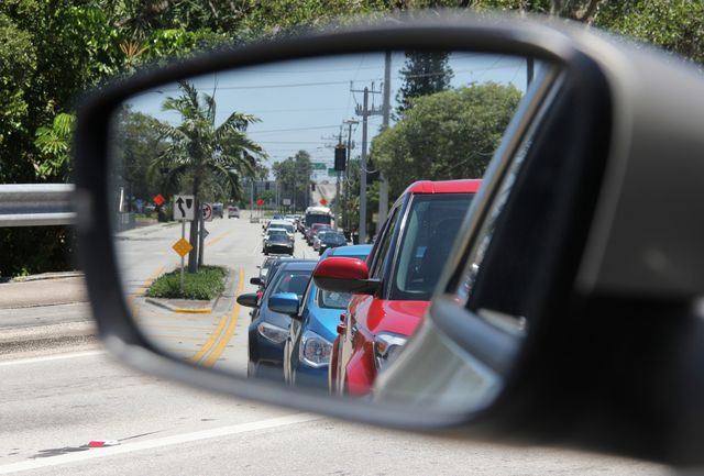 close up of side view mirror reflecting traffic