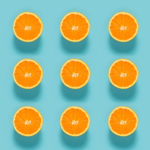 close up of sliced orange fruits on blue background