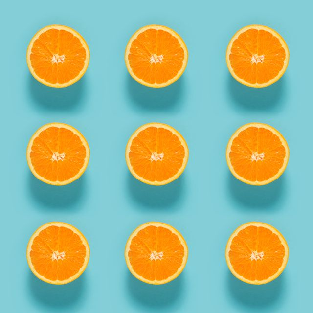 Close-Up Of Sliced Orange Fruits On Blue Background