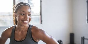 Close-up of smiling athlete looking away while standing in gym