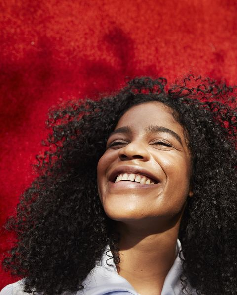 close up of smiling woman against red wall