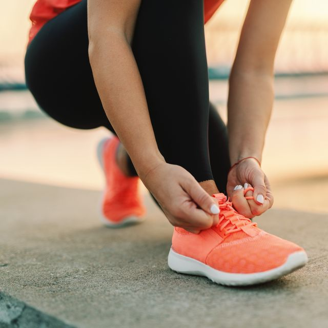 close up of sporty woman tying shoelace while kneeling outdoor, in background bridge fitness outdoors concept