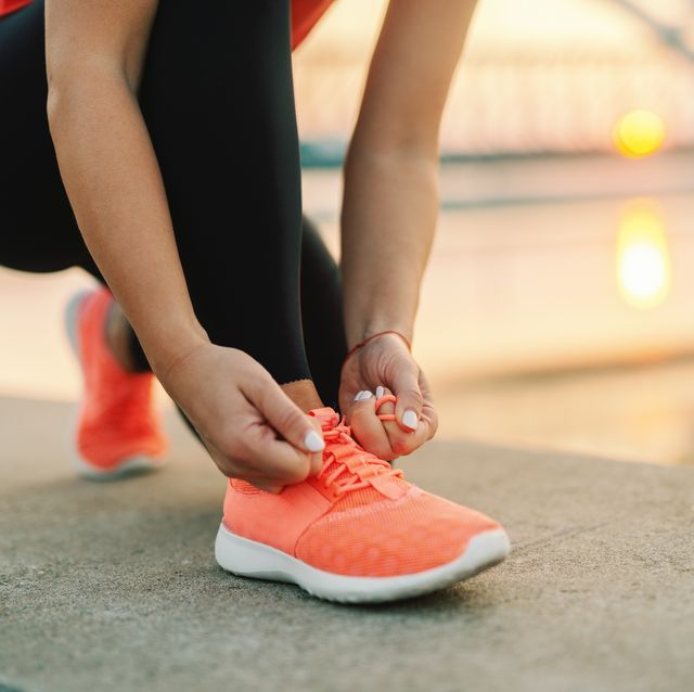 close up of sporty woman tying shoelace while kneeling outdoor in background bridge fitness outdoors concept