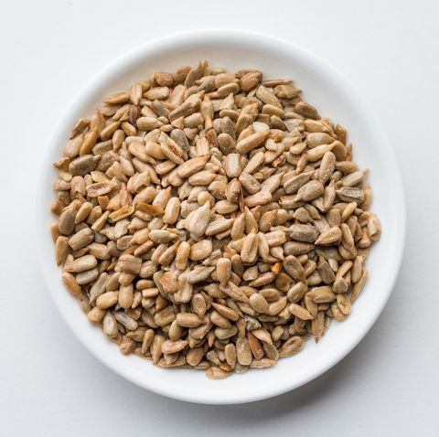 close up of sunflower seeds in bowl over white background