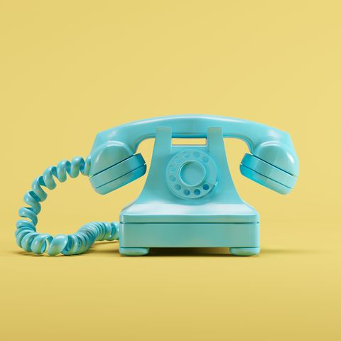 close up of telephone against yellow background