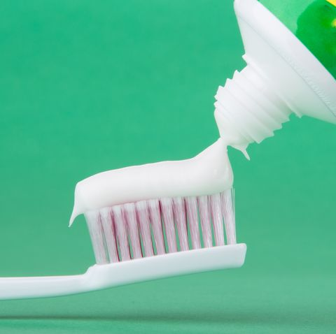 Close-Up Of Toothpaste On Toothbrush Over Table