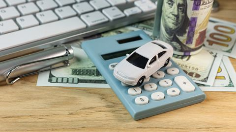 Close-Up Of Toy Car And Calculator By Keyboard On Table