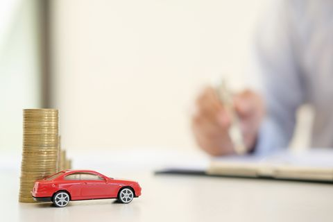 Close-Up Of Toy Car And Coins By Insurance Agent On Table At Office
