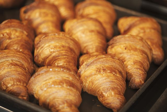 close up of tray of freshly baked croissants in a bakery