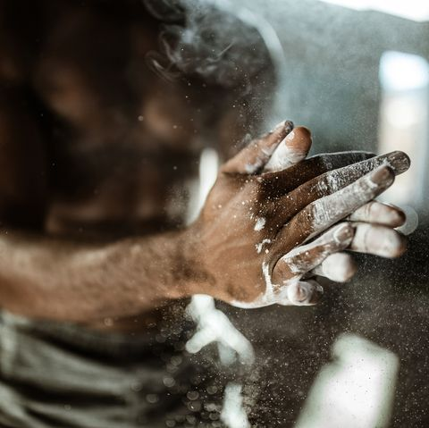 Close up of unrecognizable athlete preparing his hands with powder.