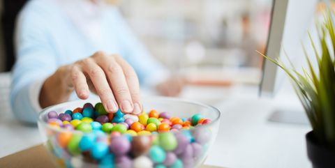 close up of unrecognizable businesswoman sitting at table and eating sweet beans while working in office