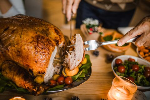 Close up of unrecognizable man carving roasted Thanksgiving turkey.