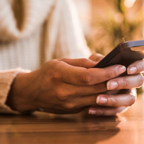 Close up of unrecognizable woman text messaging on cell phone.