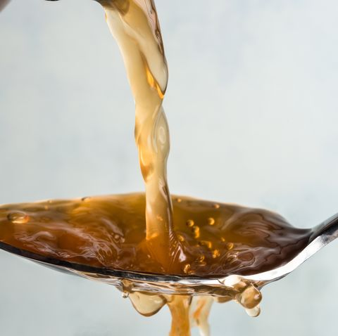 close up of vinegar pouring in spoon against white background