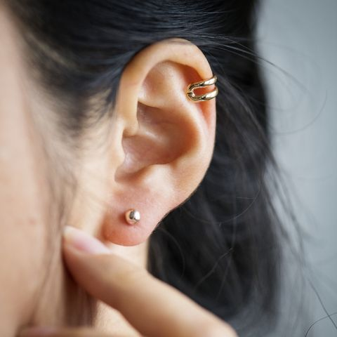 close up of womans ear with earrings