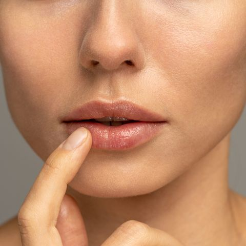 close up of woman applying moisturizing nourishing balm to her lips with her finger to prevent dryness and chapping in the cold season