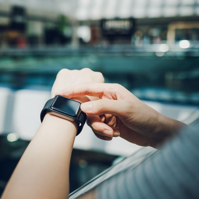 close up of woman checking the shopping list on smart watch in a shopping mall