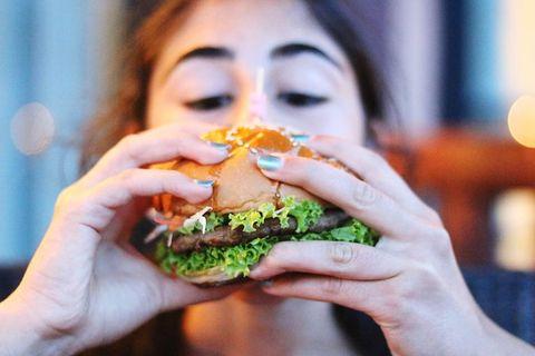 Close-Up Of Woman Eating Burger