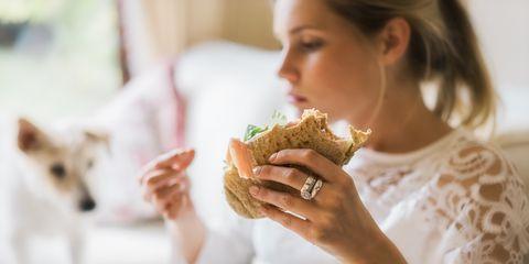 close up of woman eating food at home