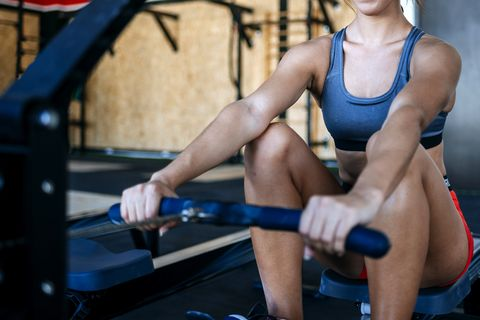 Close-up of woman exercising with a rowing machine in gym
