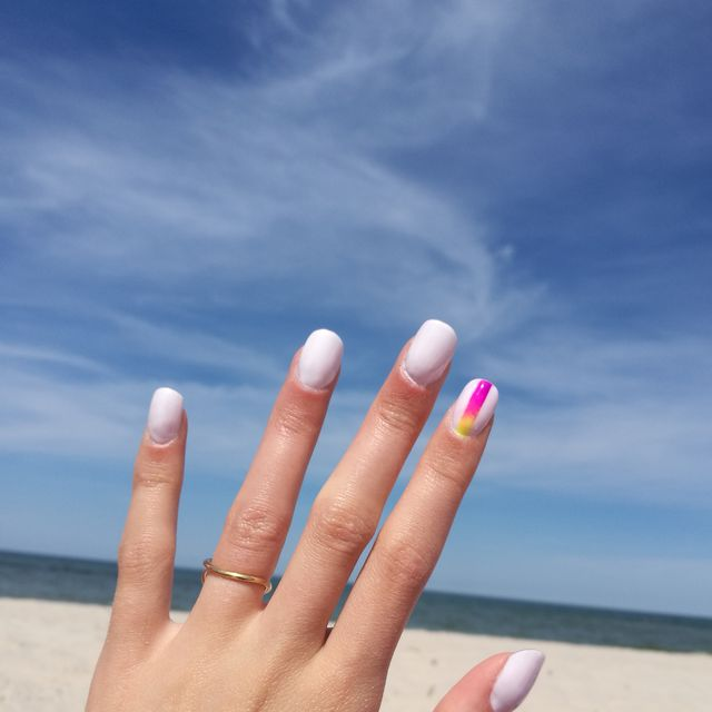close up of woman fingers with nail art manicure in white colour