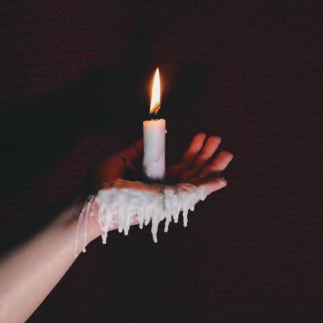 close up of woman hand holding lit candle against black background