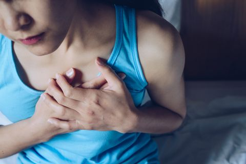 close up of woman having suffering from chest pain or heart attack