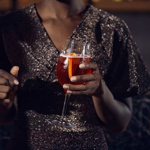 close up of woman holding a cocktail glass in a bar