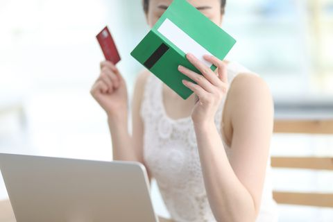 Close up of woman holding bank book and credit card