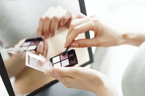 Close up of woman holding eye shadow pallet