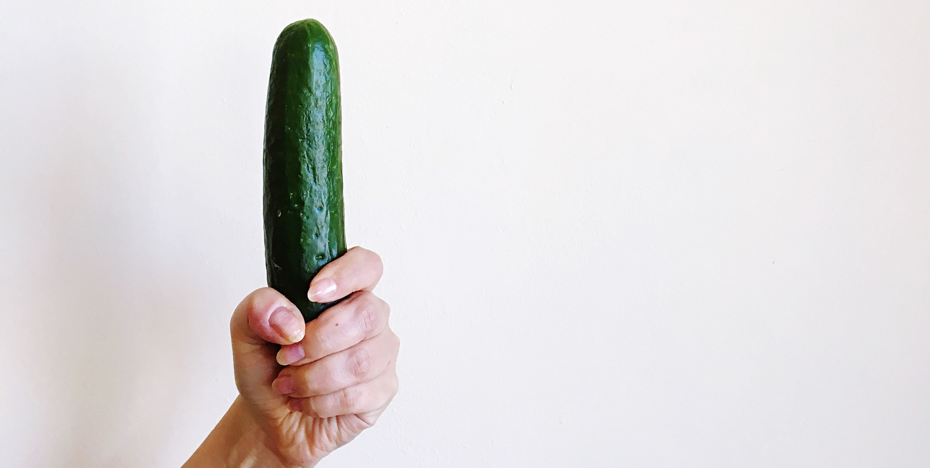 Close-Up Of Woman Holding Zucchini Against White Background