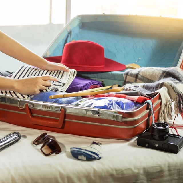 close up of woman packing luggage on bed