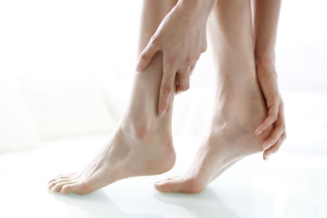 close up of woman rubbing feet