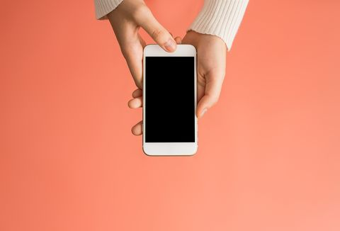 close up of woman using mobile phone over pink background