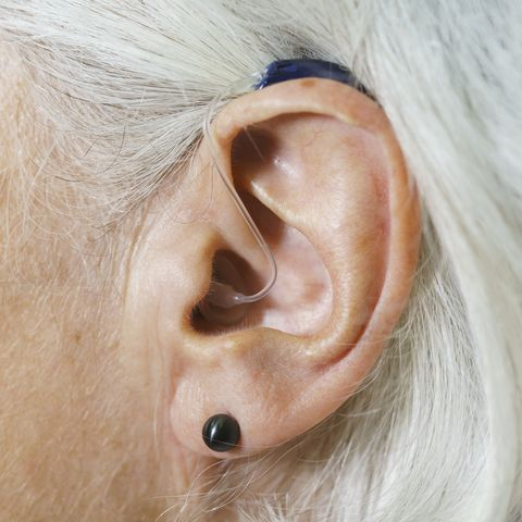 Close-up of woman with gray hair wearing hearing aid